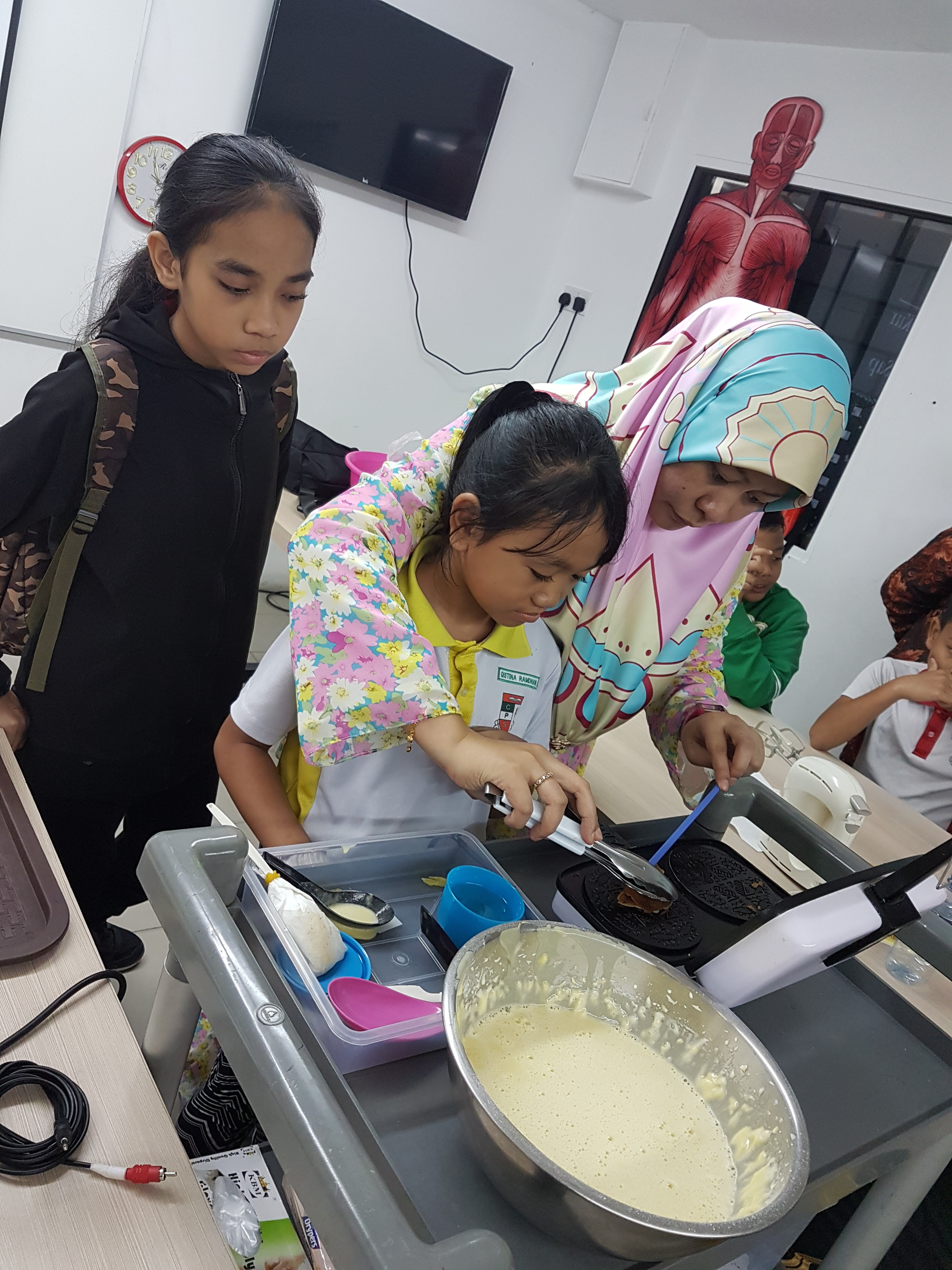 5 Pupils trying out their Home Economics CCA.jpg